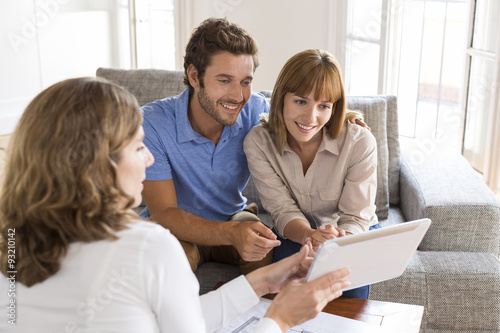 Valokuva Real-estate agent presenting to a couple a project property on tablet PC