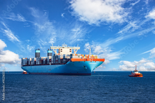Fotografia  Holowniki wspomagające statek kontenerowy do portu.