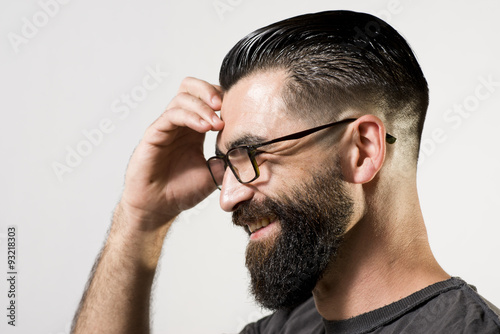 Portrait of smiling hipsterwith hand on his head