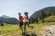 Austria, Tyrol, Tannheim Valley, young couple jogging in alpine landscape