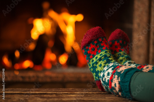 Deurstickers Ontspanning Feet in woollen socks by the Christmas fireplace. Woman relaxes by warm fire and warming up her feet in woollen socks. Close up on feet. Winter and Christmas holidays concept.