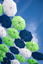 Group Of Green, Blue, And White Umbrellas Against Blue Sky