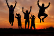 Young happy family jumping silhouettes at sunset