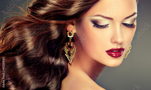 Beautiful model with curly hair and large earrings . fashion trend image ,the girl with blue eyes , fashion makeup and  