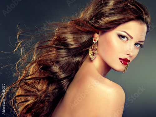 Beautiful model with curly hair and large earrings . fashion trend image ,the girl with blue eyes , fashion makeup and   earrings jewelry