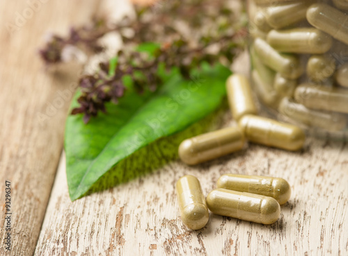 Fotografia  Herb capsule with green herbal leaf on wood