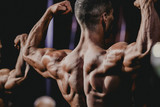 performance athlete bodybuilder to competition. demonstration of biceps your arms from behind closeup