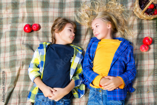 Papiers peints Attraction parc Happy smiling boy and girl lying together on rug. picnic in park