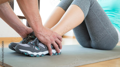 Personal trainer helping young attractive woman doing crunches in the gym