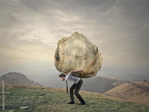 Fotografia  Businessman carrying a big rock