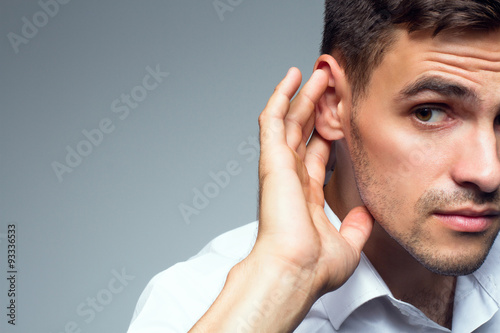 Photo  Young businessman holds his hand near ear.Close up portrait