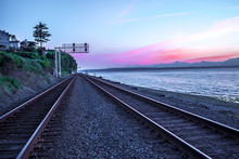 Train Tracks Vanishing Into Distance On Ocean Beach At Sunset With Pink And Purple Mountain Range In Background