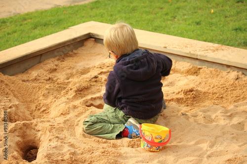 Fotografie, Obraz  Ein kleiner Junge spielt im Sandkasten