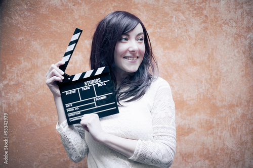 Plagát  Young woman in 70s hippie style smiling with clapperboard