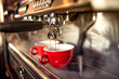 canvas print picture - coffee machine preparing fresh coffee and pouring into red cups at restaurant, bar or pub.