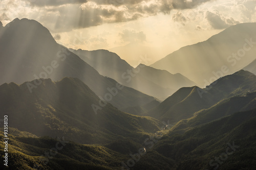 Tuinposter Heuvel Shadow of mountain layer with sun ray silhouette shot
