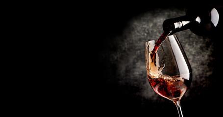 Fototapeta Do steakhouse Pouring wine on black