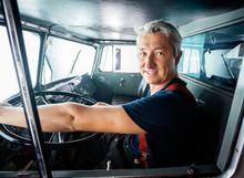 Confident Fireman Driving Firetruck