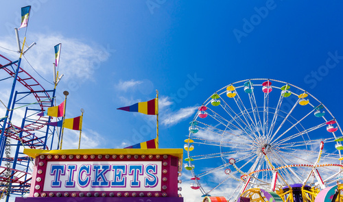 Ticket Booth and Carnival Rides against blue sky