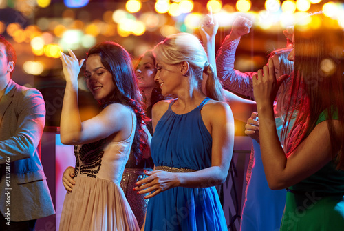plakat group of happy friends dancing in night club