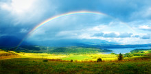 Meadow And Lake With Mountain On Background  A Rainbow .