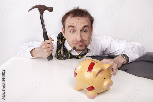 Fotografie, Tablou Businessman is trying to break the piggybank with hammer