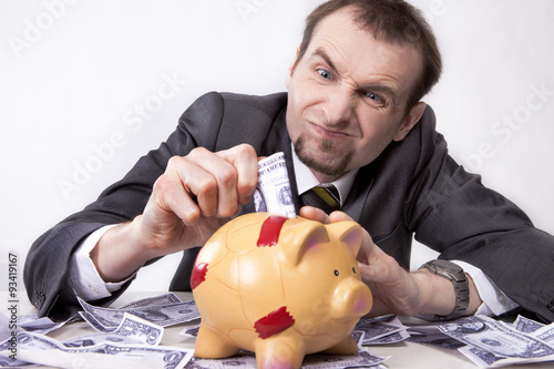 Stingy businessman is trying to save his money Canvas Print