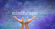 Zen Mindfulness Meditation - Female hands reaching up towards the word 'Mindfulness' floating above surrounded by a relevant word cloud on an ethereal blue night sky background