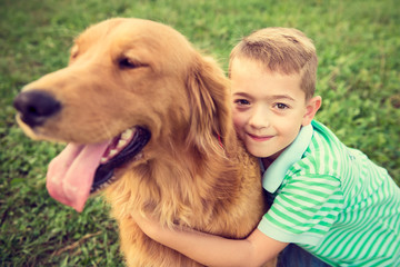 FototapetaCute little boy hugging his golden retriever pet dog