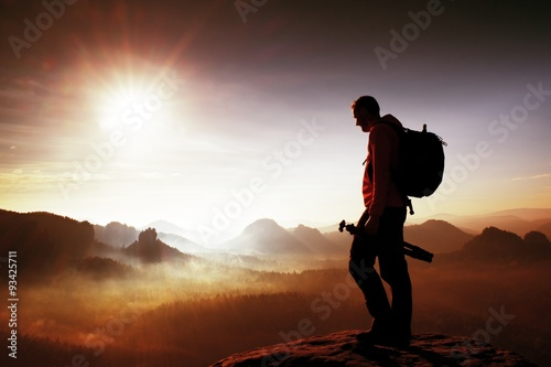 Poster Rood paars Silhouette of photographer overlooking a blanket of fog over valley to sun