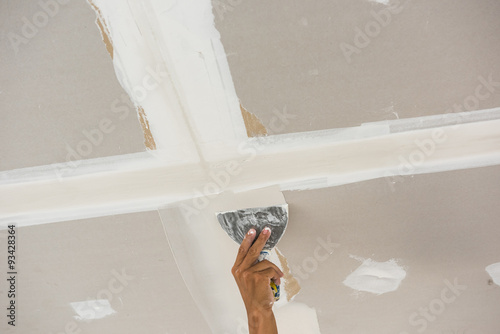 Man Hand With Trowel Plastering A Ceiling Skim Coating