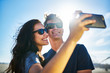 smiling couple taking selfies with smartphone on the sunny beach