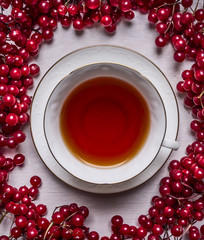 Fototapetawhite cup of tea on a saucer on a white wooden background frame of red berries Viburnum close up top view