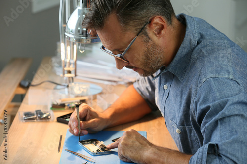 Fototapeta Man repairing broken smartphone in workshop obraz