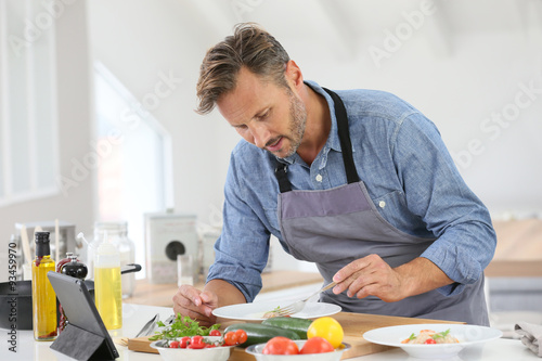 Poster Cuisine Man in kitchen cooking dish and using digital tablet