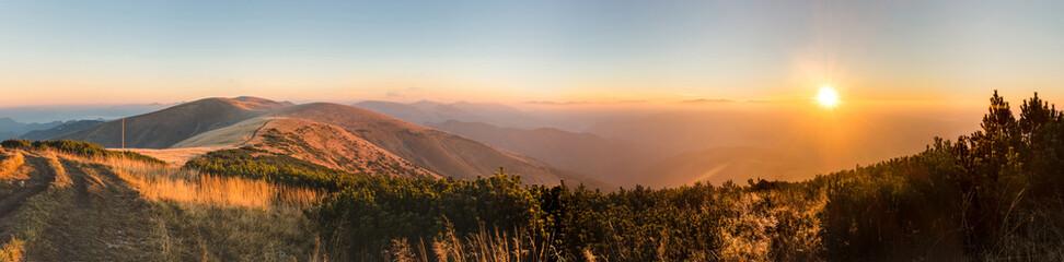 Panorama of amazing sunrise on mountain ridge