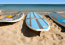Surf Boards In A Row On Sandy Beach By The Sea.