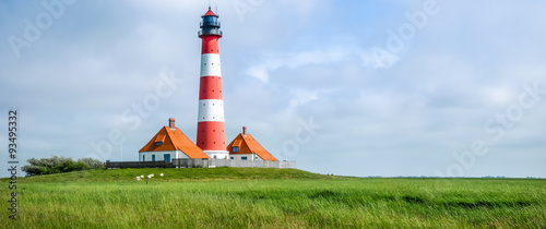 Foto op Aluminium Vuurtoren Traditional lighthouse at North Sea with blue sky and clouds