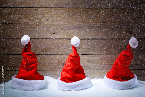 Santa hats in snow with wooden background - 93501579