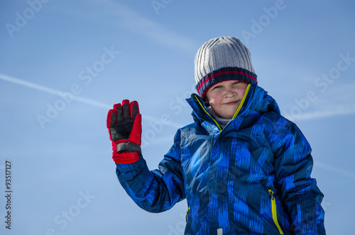 Photographie A child in winter clothes posing on a background of blue sky.