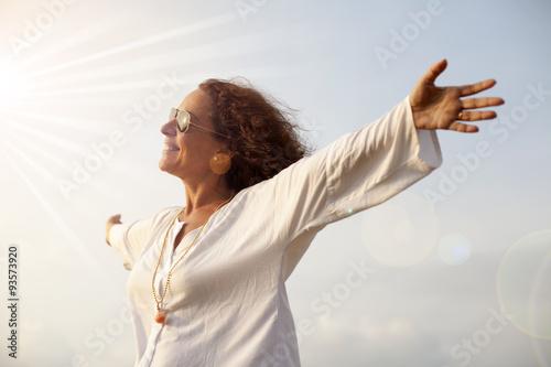 Photo Mujer con los brazos abiertos hacia el sol radiante