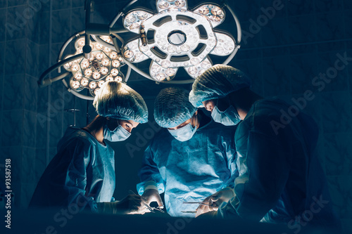 Fotografie, Tablou Surgeons team working with Monitoring of patient in surgical