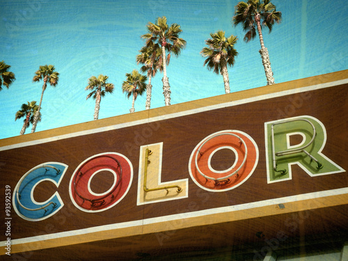 aged and worn vintage photo of retro neon color sign with palm trees