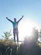 Successful man raising arms after cross track running on summer