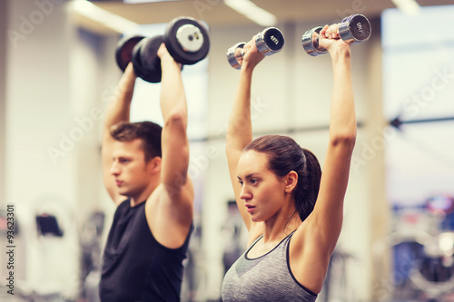 Foto op Plexiglas Fitness smiling man and woman with dumbbells in gym