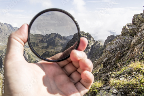 Fotografia, Obraz  Hand puts a polarization filter to the camera, in the background a beautiful lan