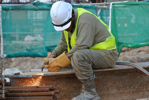Construction workers cutting metal using blowtorch at the construction site Wallpaper Mural