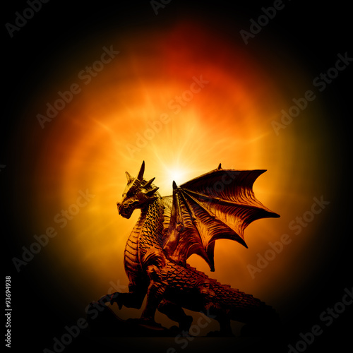 Fotografie, Tablou  a statue of dragon over orange mysterious backround