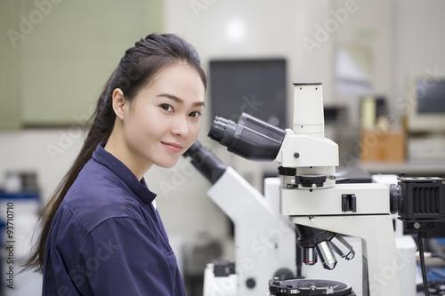 Fotografia  female scientist looking in microscope in laboratory Laboratory