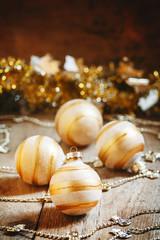 Obraz na płótnie Canvas Golden Christmas balls on decorated table, festive postcard, sel